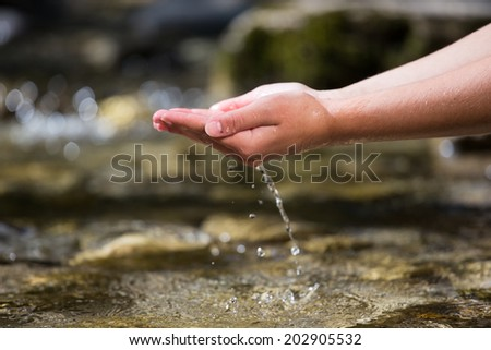 The hands taking out the water from the river - stock photo
