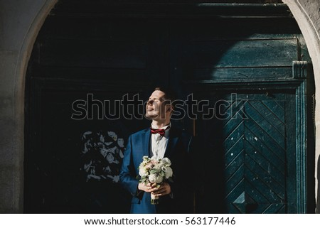 The handsome groom keeps a wedding bouquet