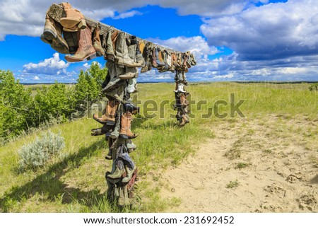 The hanging cowboy boots at the Great Sand Hills near Sceptre, Saskatchewan.  These old hanging boots are a memorial to John Booth who was a local rancher and lived in the area his entire life. - stock photo