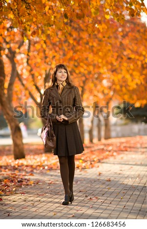 The happiness mature beautiful woman, walking outdoor in park, autumnal day - stock photo
