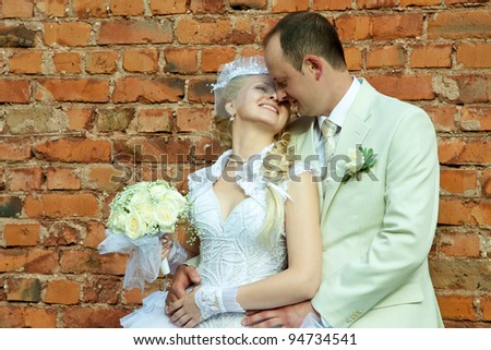 The happy bride and groom leaning against the wall of brick; wedding day - stock photo