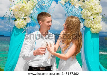 The happy bride and groom with white doves on a tropical beach under palm trees. Wedding and honeymoon in the tropics. - stock photo