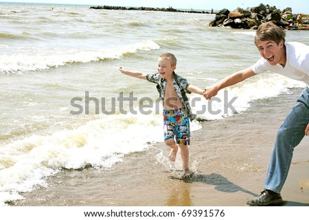 The happy child and teenager runs on seacoast - stock photo