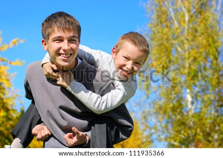The happy child sits on the teenager shoulders - stock photo