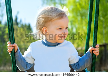 the happy child swinging on a swing - stock photo