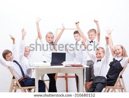 The happy children raising hands on white background - stock photo