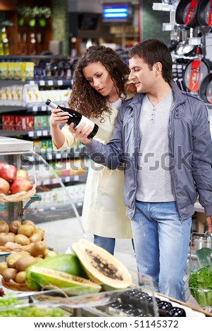 The happy couple chooses a wine bottle in shop - stock photo