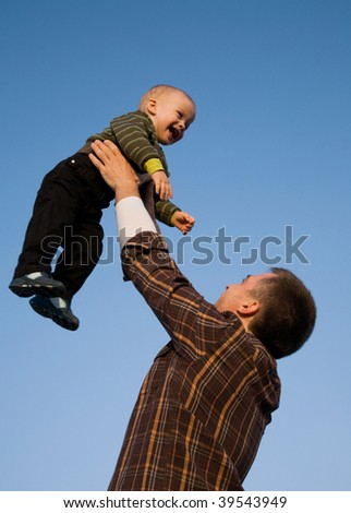 The happy daddy lifts on hands of the little son against the blue sky