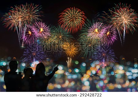 The happy family looks celebration fireworks on the night sky