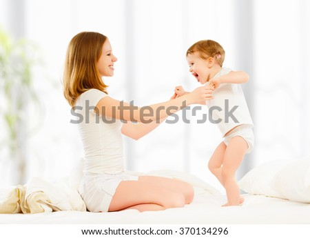 The happy family mother and child daughter playing and laughing kissing in bed - stock photo