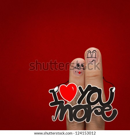 the happy finger couple in love with painted smiley and hold word love you more - stock photo
