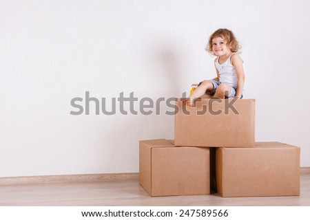 The happy little girl sits in a room on the boxes. Moving, purchase of new habitation or repair of a room.