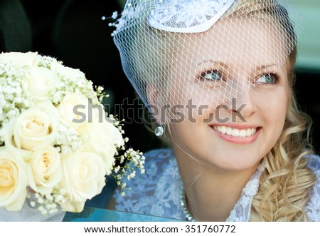 The happy smiling bride sitting in the automobile and holding her wedding posy