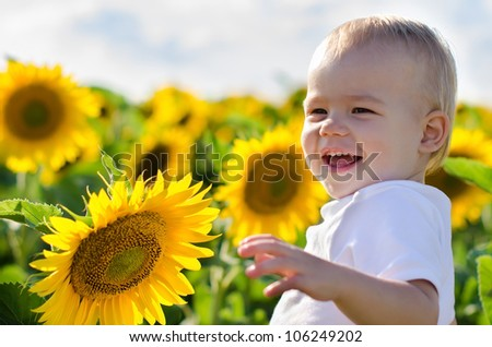 The happy smiling little boy with a sunflower