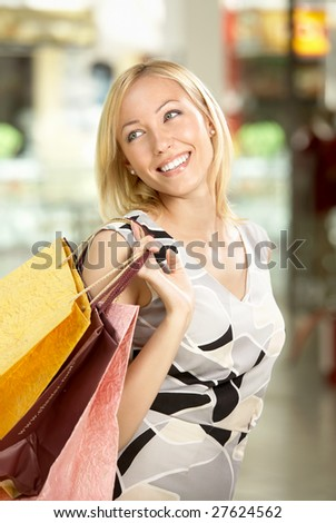 The happy woman in shop with packages through a shoulder - stock photo