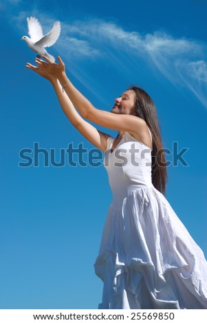 The happy woman releasing a pigeon in sky - stock photo