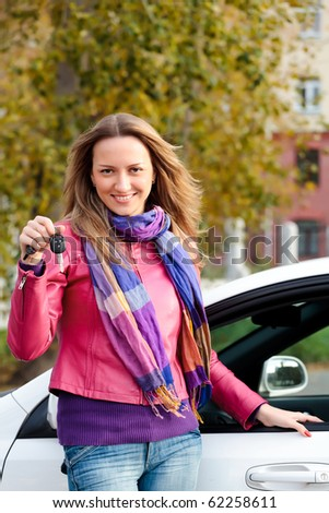 The happy woman showing the key of her new car. - stock photo
