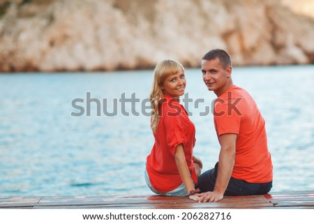 The happy young couple walking on a wooden pier on the seashore and are dressed in fashionable clothes. Having fun.