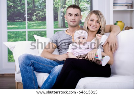 the happy young family inside the flat - stock photo