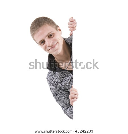 The happy young man on white background behind the white stand - stock photo