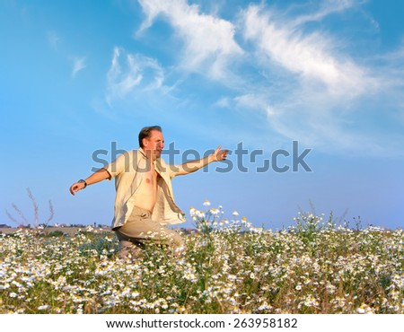 The happy young man runs in the field of camomiles  - stock photo