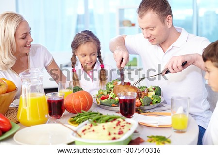 The head of family cutting Thanksgiving poultry - stock photo