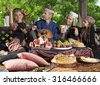 The head of the family playing mandolin during breakfast. Whole family dressed in Central Asian clothes