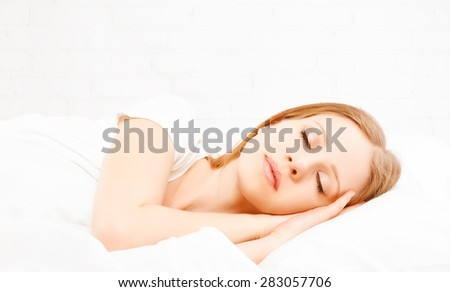 The Healthy young beautiful woman sleeping in white bed - stock photo