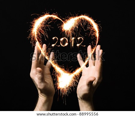 The heart and the number 2012 from the Bengal fire in the hands of man. - stock photo