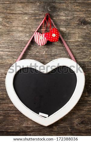 The heart shape chalkboard over old wooden background - stock photo