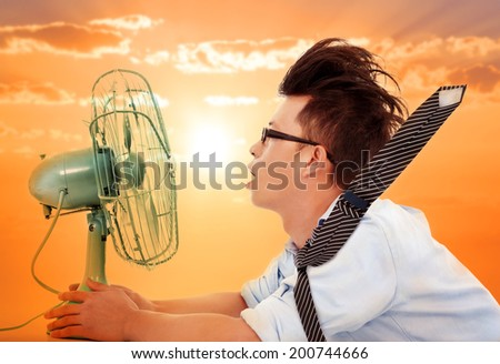 the heat wave is coming,business man holding a  electric fan - stock photo