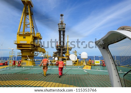 The helicopter landing officer are walking back after take care passenger to embark helicopter at oil rig platform is in the gulf of Thailand. - stock photo
