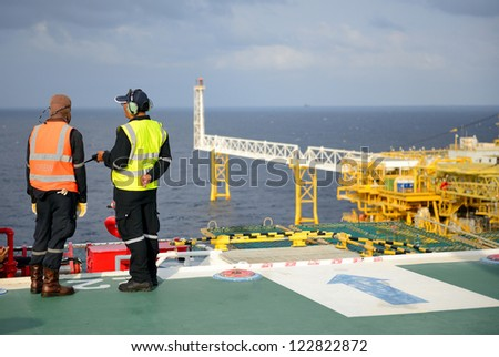The helicopter landing officers are on the oil rig. - stock photo