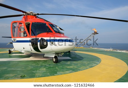 The helicopter park on oil rig to pick up worker with gas flare and blue sky backgroung - stock photo