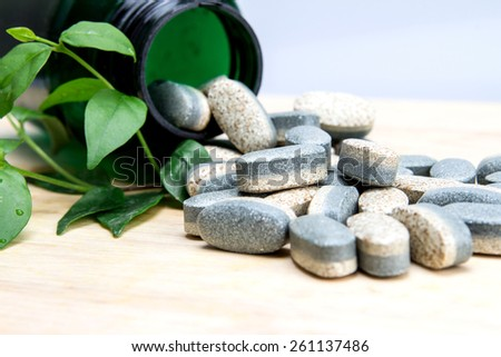 The Herbal Supplement vitamin pills or tablets on wooden plate - stock photo