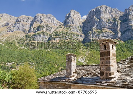 The high cliffs of Papigo (called towers) behind the typical stone house of Zagori area, Greece