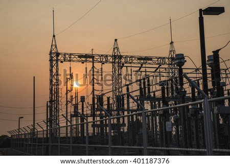 The high voltage equipment in the outdoor electrical substation yard during sunrise