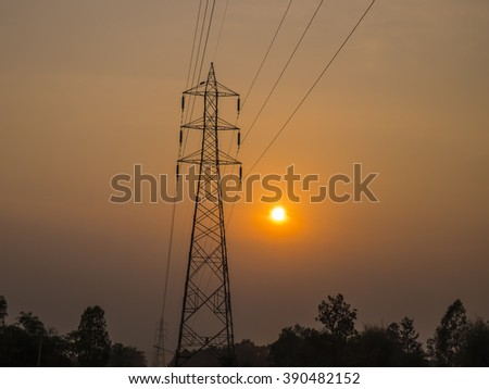 The high-voltage tower against sunset background.