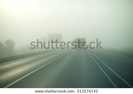 The highway in the fog. The truck rides ahead. Overcast and storm weather.