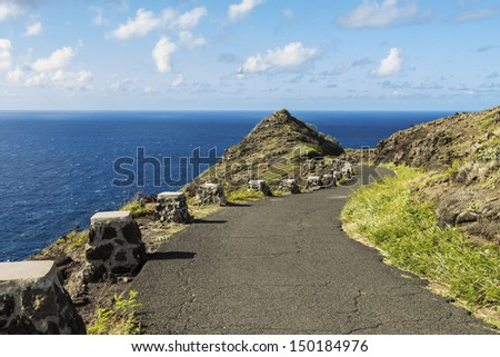 The hiking trail leading down Makapuu Point with an expansive view of the Pacific Ocean - stock photo