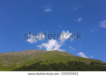 The hill in bright clear fine day with the blue sky and clouds. summer landscape. mountain landscape. bright sunny clear day  - stock photo