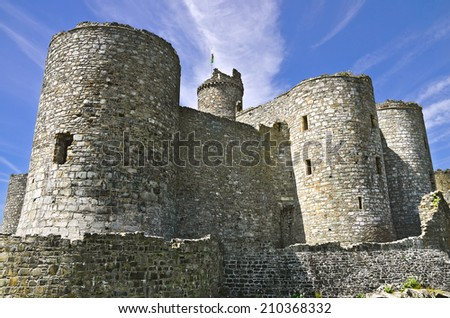 The historic Harlech Castle, Wales, a medieval fortress with massive round towers and ancient stonework, stands against a blue sky with streaky white clouds.  - stock photo