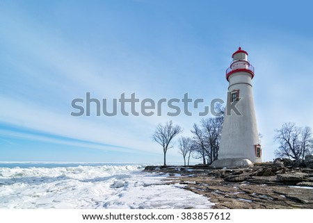 The historic Marblehead Lighthouse in North west Ohio sits along the rocky shores of the frozen Lake Erie. Seen here in winter with a colorful blue sky and snow and ice on the ground. - stock photo