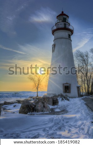 The historic Marblehead Lighthouse in Northwest Ohio sits along the rocky shores of Lake Erie. Seen here at sunrise in winter with snow and ice on the ground. - stock photo