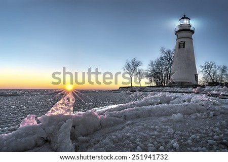 The historic Marblehead Lighthouse in Northwest Ohio sits along the rocky shores of the frozen Lake Erie. Seen here in winter with a colorful sunrise, snow on the ground and a seagull flying by. - stock photo