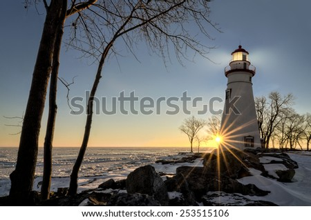 The historic Marblehead Lighthouse in Northwest Ohio sits along the rocky shores of the frozen Lake Erie. Seen here in winter with a colorful sunrise and snow on the ground. - stock photo