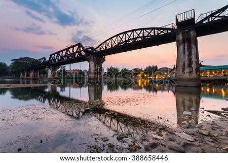 The historic railway bridge over Kwai river which built by Japanese soldiers at sunset, Kanchanaburi, Thailand - stock photo