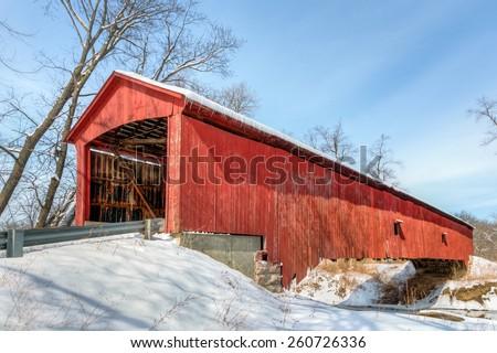 The historic red Oakalla Covered Bridge crosses Big Walnut Creek in rural Putnam County Indiana. - stock photo