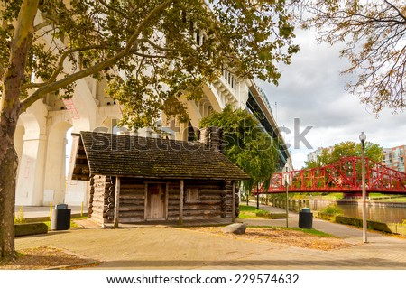 The historic Settler's Landing cabin in Cleveland's Heritage Park stands under the Veterans Memorial Bridge over the Cuyahoga River - stock photo