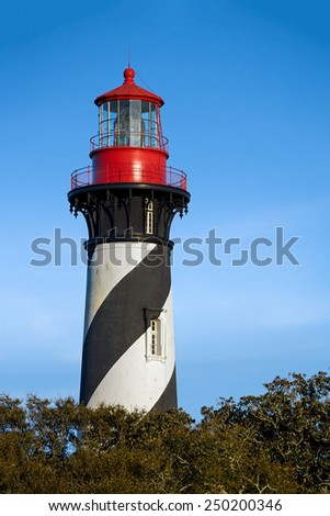 The historic St. Augustine Lighthouse rises above Florida's Atlantic coast. - stock photo